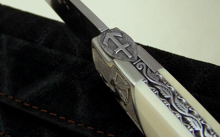 Couteau motif sagittaire ressort ciselé feuilles de houx manche ivoire de mammouth lame rwl 34